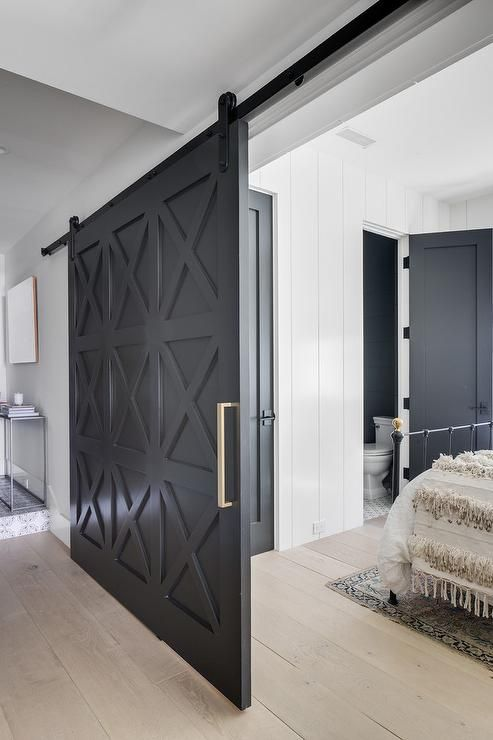 A Black Barn Door On Rails Slides Open To A Bedroom Fitted With Wide Plank Gray Stained Wood Floors Comple Interior Barn Doors Barn Doors Sliding Barnyard Door
