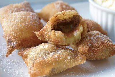 """Chocolate Banana Wontons - Smear a tsp of peanut butter in the center of a wonton wrapper. Add a slice of banana and top w/a piece of chocolate. Dip your finger into water and trace the edge of the wrapper. Fold the corners of the wonton into the center like an envelope, pinch and seal. In a small pot, heat up vegetable oil (to 350°F) about 3"""" deep. Add 3-4 wontons at a time, fry for 1-2 min until golden brown. Place on paper towel to absorb excess oil. Dust w/powdered sugar & serve w/ice…"""