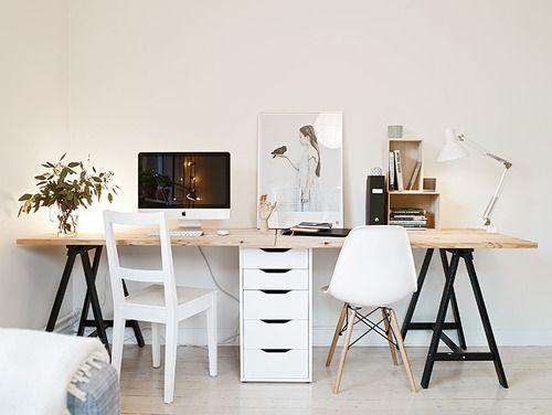 Mesa grande com tampo em madeira natural, cavaletes pretos e gaveteiro branco ajudando na sustentação: