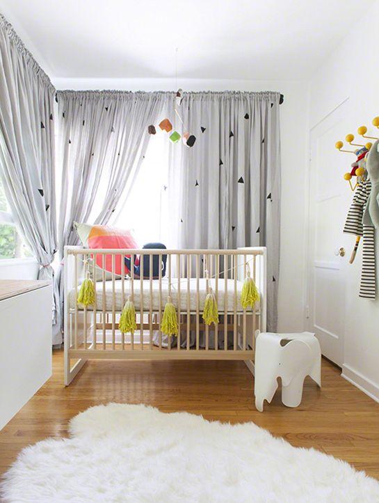Prefere as paredes brancas e móveis em madeira? A cortina estampada pode ser o toque criativo, unido a outros elementos, como um mobile colorido para o berço.