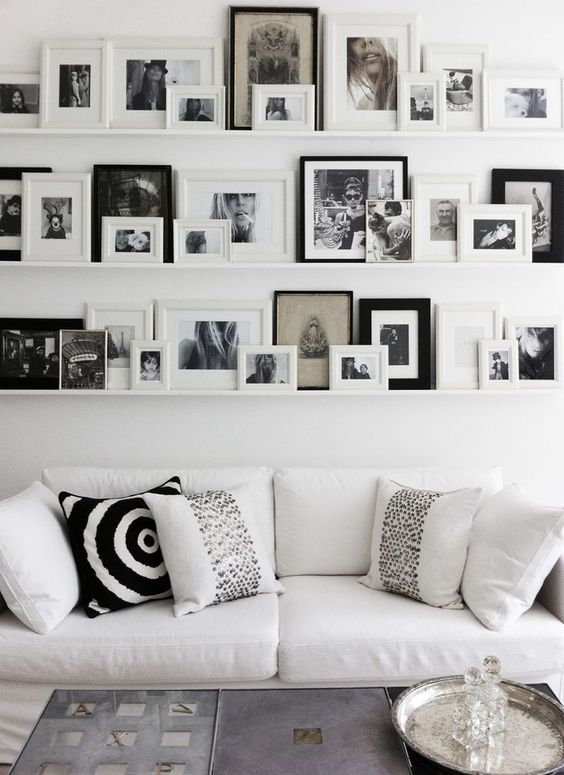 gallery-wall-annika-von-holdt - Gallery wall using shelves from Ikea to rest frames on - Love that you can change out photos so easily.: