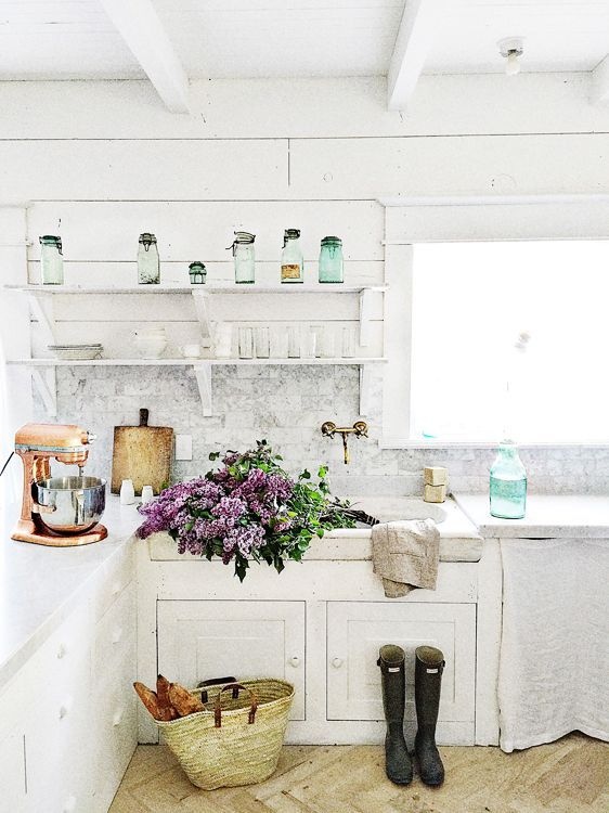 White kitchens design ideas: French farmhouse style white kitchen with white cabinets, carrara marble, and herringbone floors. Dreamy Whites.