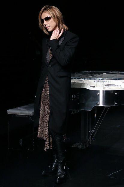 黒いロングコートを着てピアノの前に立っているXJAPAN・YOSHIKIの画像