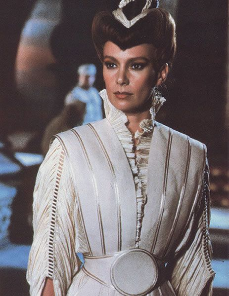 Dune - Francesca Annis as Lady Jessica Atreides wearing a white pleated dress with ruffled collar, open work embroidered details on the gathered sleeves and white and silver vest with corset belt. The costumes were designed by Bob Ringwood.