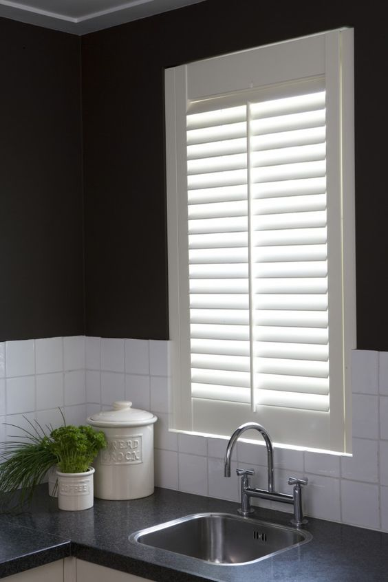 Jasno shutters vóór het keukenraam. Je kunt eenvoudig de hoeveelheid privacy en lichtinval naar behoefte regelen met de verstelbare lamellen. Bovendien zorgen shutters voor een goede akoestiek en zijn ze gemakkelijk in onderhoud.