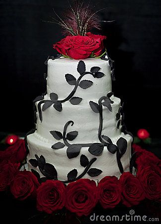 A tiered wedding cake in black and white with red roses and a peacock feather top on a black bakground.