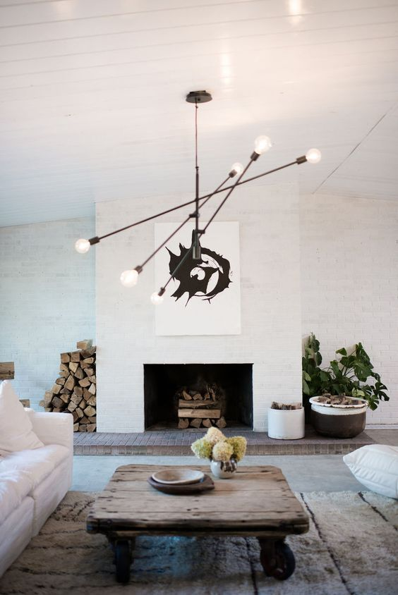 Minimal organic meets luxury style in this updated mid-century living room by #Leanne Ford. Black Sputnik chandelier, rustic coffee table, and white sofa.