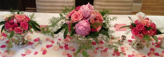 Roses and peonies in mercury glass surrounded by rose petals and silver baby rattles!