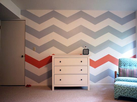 Accent walls don't always have to be a solid colour. Love how this room is brought together with a chevron print wall and the added element of the single orange stripe!