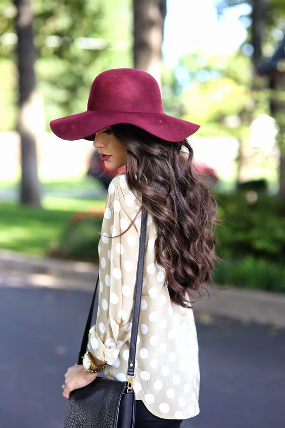 A woman walking down the street in a burgundy floppy hat with long dark brown wavy hair and red lipstick