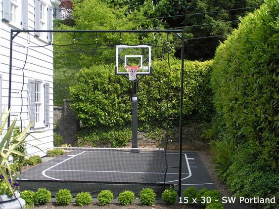 Small side yard basketball court w/ boxwood and net barriers