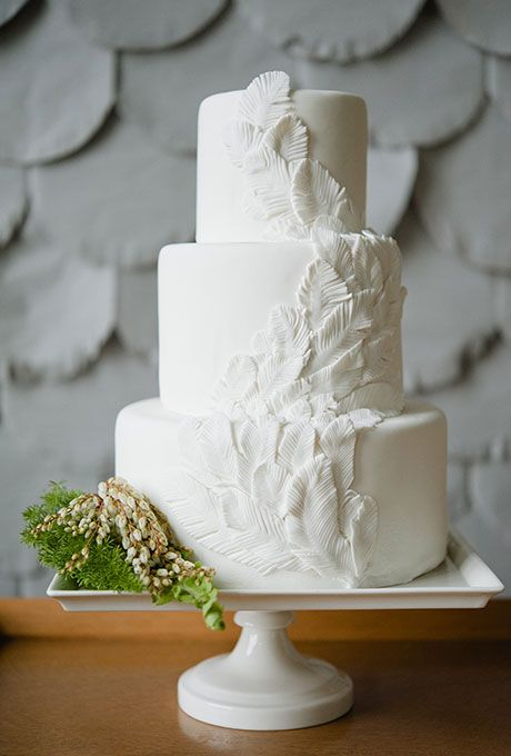 An all-white three-tiered wedding cake with fondant feathers and accented with greenery, created by Sweets Bakeshop. – @brides