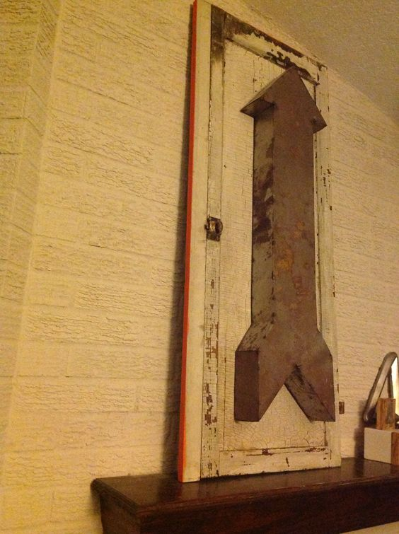 Tin arrow on old cabinet door, painted edges bright orange. Sitting on our mantle