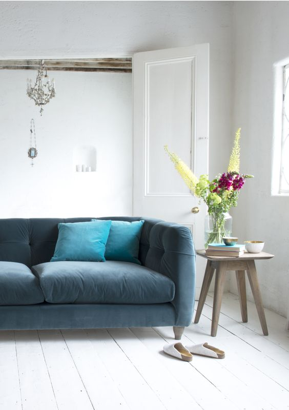 Loaf's button-backed Happy sofa upholstered in Mermaid velvet and styled with fresh blooms
