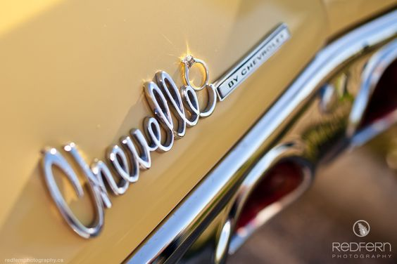 Engagement photo, engagement ring on a classic yellow Chevelle car.