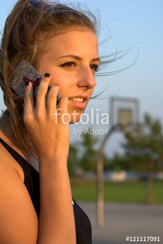 Junge Frau telefoniert draußen mit einem Smartphone, Handy, Sommer, Sonne - Fotolia - © SULUPRESS / Torsten Sukrow