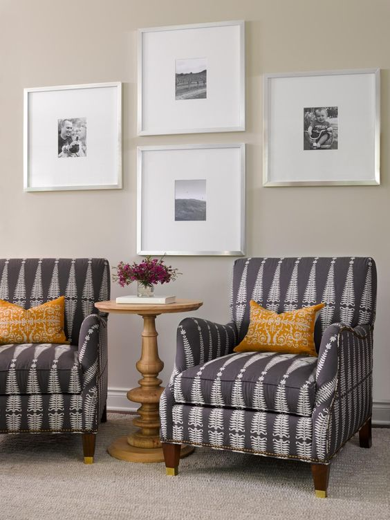 Graphic club chairs with black-and-white wall art comprise a cozy sitting area in a casual contemporary great room.