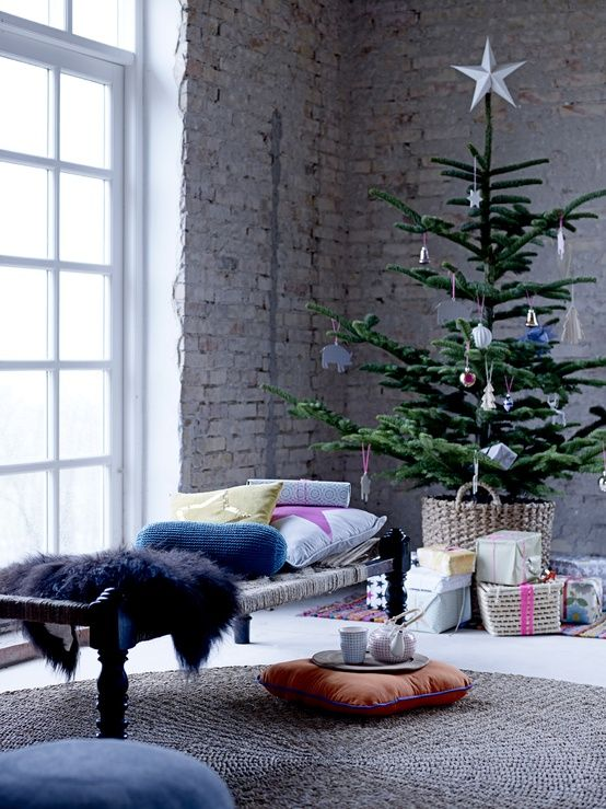 Sapin de Noël dans un panier en osier devant un mur en briques apparentes