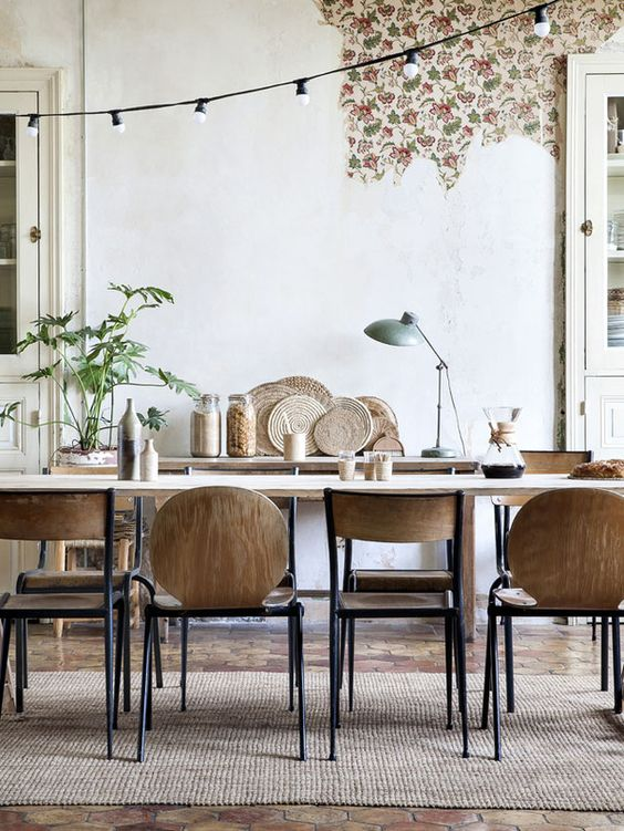 Salle à manger en bois naturel, chaises vintage et sol en tomettes