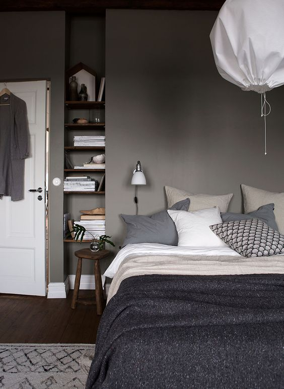 Grey bedroom with wooden shelves in a small niche