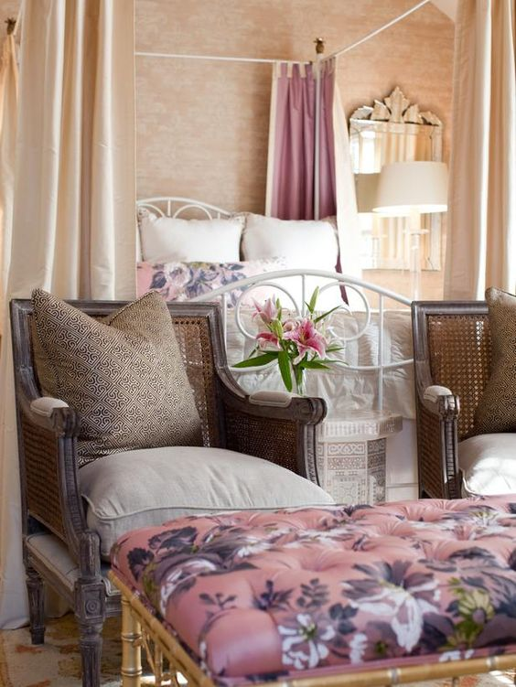 At the foot of this canopy bed sit two brown chairs. Patterned throw pillows and intricate carvings along the chair legs add interest to the room, though the sitting area is kept understated in neutral tones.