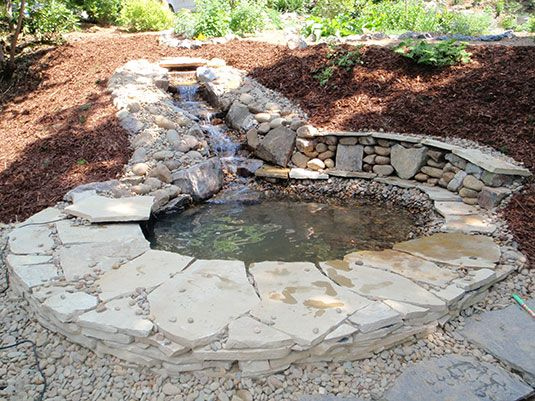 Rubble stone fountain leading into small man made pond for Stone koi pond