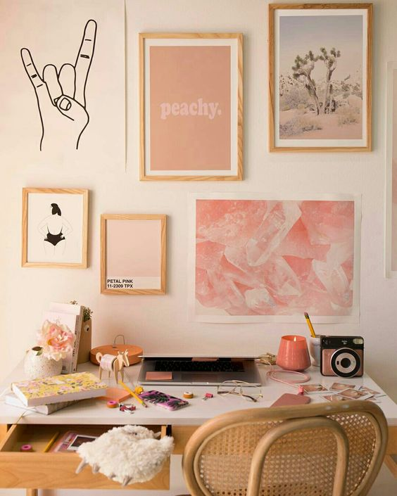 """Light pink wall with light wood frames and pink accents hanging. A hand formed into sign language """"rock on"""" painted onto wall"""