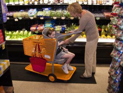 Grocery cart for special needs children makes it possible for even a child with disabilities to be part of family shopping trip.  The cart provides a safe place for the child to sit facing the caregiver.  It was invented by a mother who has a daughter with several disabilities.