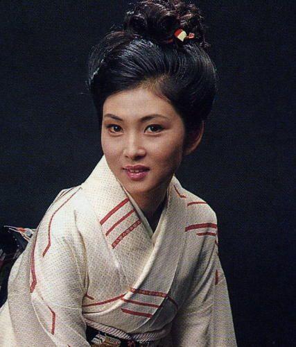 赤いラインの入った白い着物を着ている梶芽衣子の画像