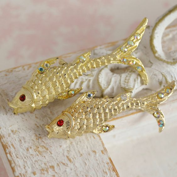 This vintage pair of brooches will make quite a splash with any outfit! Made of gold-tone metal, the two difference sizes are adorned with red