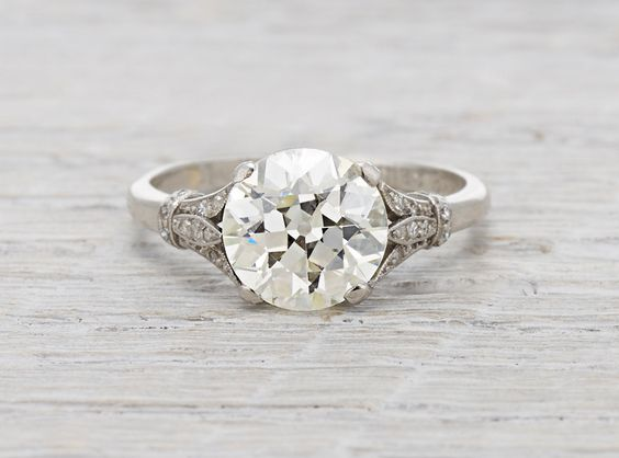 Egyptian Revival Art Deco Ring made in platinum and centered with a 2.95 carat EGL certified old European cut diamond with K-L color and VS2 clarity. Accented with french cut diamonds in the gallery and single cut diamonds on each shoulder. Low profile. Circa 1920