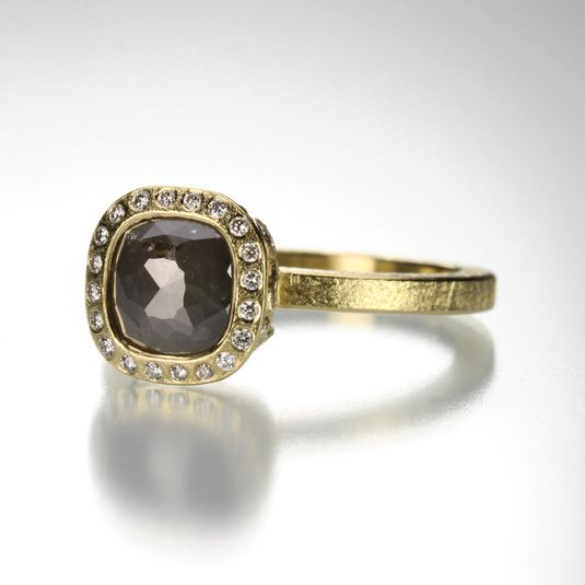 Understated and stunning, this Todd Reed ring is handcrafted from warm 18k yellow gold and set with an absolutely gorgeous black fancy cut diamond. As if the sparkle of the black diamond weren't enough, there is a halo of white brilliant diamonds to add to the cool confidence of this ring.
