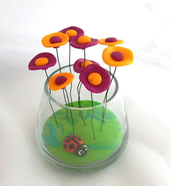 Oubliez l'arrosage et l'entretien de vos plantes vertes, oubliez les fleurs qui fânent tristement, découvrez le bouquet de fleurs miniatures en fimo !  Bouquet de fleurs en fimo sur tiges en métal dans petit pot en verre design et sa petite coccinelle.  Matières : fimo pâte polymère, verre, métal. Dimensions : Hauteur : 10 cm / Largeur : 7 cm