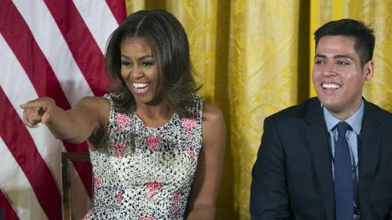 First lady Michelle Obama gestures while Brown University student Manuel Contraries, the son of two Mexican immigrants, looks on, during an East Room event to welcome more than 130 college-bound students from across the county to participate in the 2015 Beating the Odds Summit at the White House in Washington, Thursday, July 23, 2015. The summit is part of the first lady's Reach Higher initiative. (AP Photo/Cliff Owen)