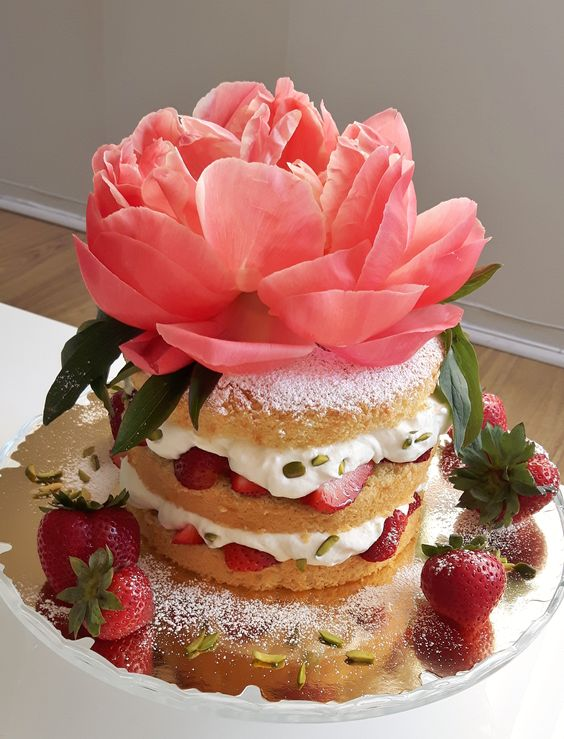 """It's strawberry time! Right now these """"berries from the earth"""" as they are called in Germany (Erdbeere) are ready to harvest and have a wonderful sweet and juicy taste. Time to get creative in the kitchen and fill the fridge with refreshing summer treats :) Basically, this naked cake contains anything but healthy things. Well, and there's this beautiful decorative blossom on top which invites to a summerly Kaffee & Kuchen gathering à la German Gemütlichkeit. © www.revelationtreats.com"""