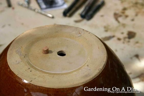 Drill a hole in a ceramic pot for drainage.  Garden Art