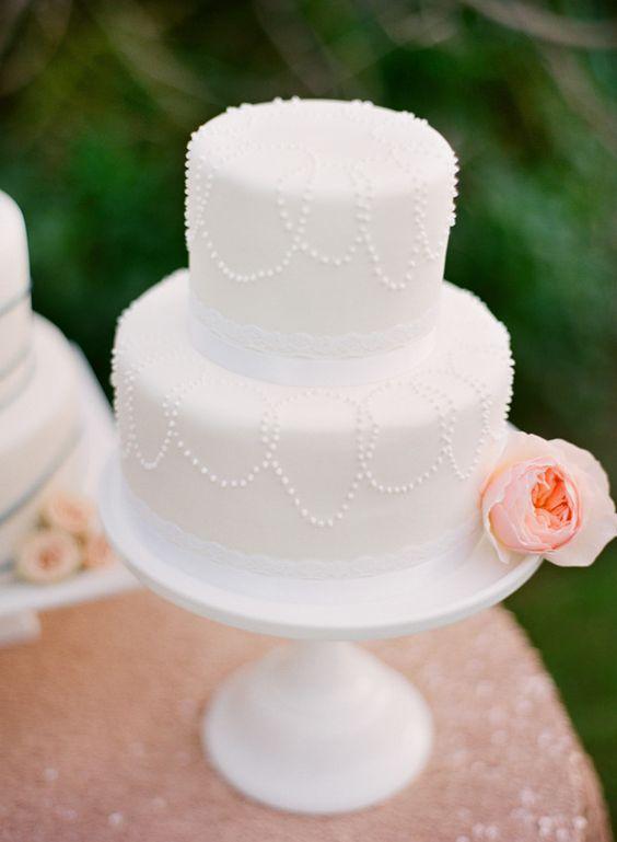 Bolo de casamento branco, pequeno, decorado com rosa em tom salmão.