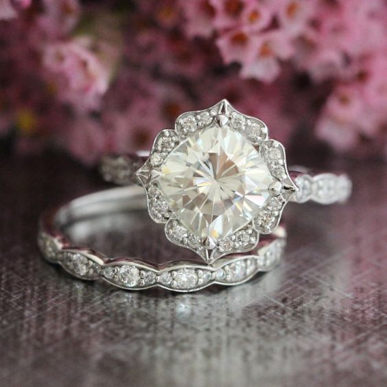 This bridal wedding ring set showcases a floral moissanite engagement ring with a 8x8mm cushion cut forever brilliant moissanite set in a solid 14k