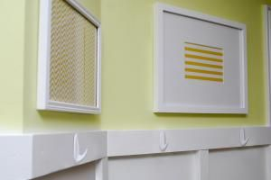 Hang Command™ Designer Medium Hooks to the top of white beadboard.