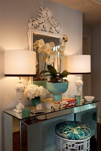 Mirrored console + white bamboo stool + matching lampshades with black trim + aqua colored accents +  fresh floral bouquets