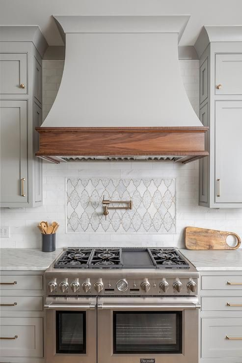 Light Gray French Hood With An Oak Trim In A Transitional Kitchen Cooktop Above A Thermador Range Flanked B Kitchen Hood Design Kitchen Cooktop Country Kitchen