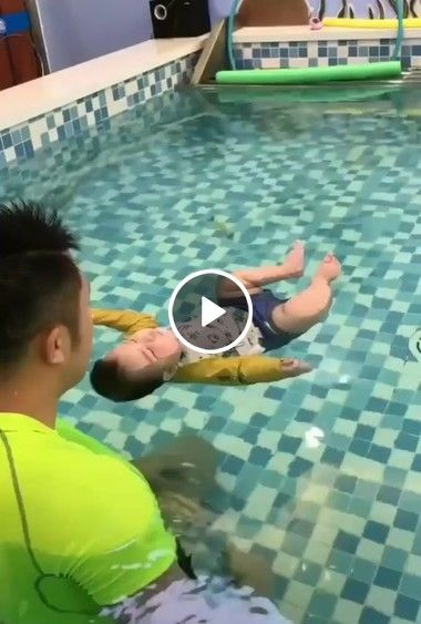 Criança nadando na piscina com seu pai