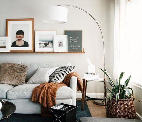 Lampada minimal dal design anni '60 come il tavolino, divano chiaro e mensola super-lunga per disporre tanti, tanti, ma proprio tanti quadri.
