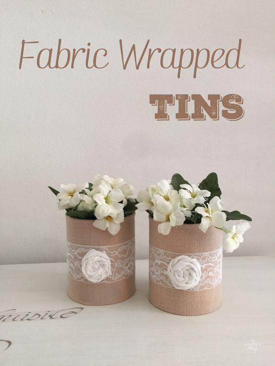 Latas vacías forradas con tela, una puntilla y una flor hecha con un retal de tela. Decoración fácil y económica