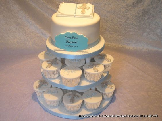 Baptism cake and cupcake tower. The top cake is a simple round cake with bible topper. The cupcakes are white iced with a selection of silver crosses or childs name.  Finished with swirl effect bases with a blue trim and plaque