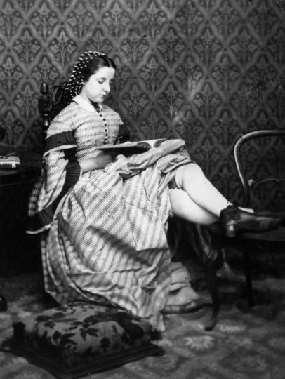 Circa 1865:  A Victorian girl reads a book, her skirts hitched up to show her thick, knee length sto