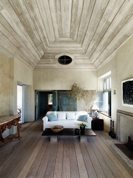 "Living room with #ovalwindow, rustic weathered wood pale ceiling, and luxurious #minimaldecor by #AxelVervoordt. From Flammarion's ""Axel Vervoordt: Living with Light"""