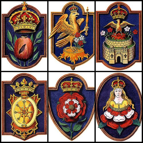The six badges, Personal Emblems, of the wives of Henry VIII.-Left to right:   Katharine of Aragon: a crowned Pomangranate, native of Spain.  Anne Boleyn: a crowned falcon, the Boleyn falcon.  Jane Seymour: a crowned pheonix, mythical creature representing immortality,  Anna of Cleves: The badge of Cleves.  Kathryn Howard: The Tudor Rose.  Catherine Parr: Tudor rose sprouting a crowned maiden.: