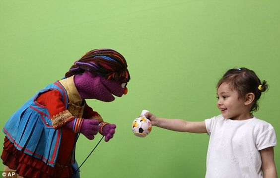 Zari, whose name means 'shimmering' in Afghanistan's two official languages, Dari and Pashtu - made her debut on the Afghan version of the show, 'Baghch-e-Simsin', meaning 'Sesame Garden', on Thursday. She is pictured here playing with a child on the set
