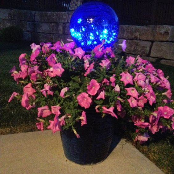 Use a gazing ball, put a string of 50 lights inside, place in middle of pot and plant flowers around.
